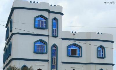 Maison omanaise blanche aux vitraux bleus